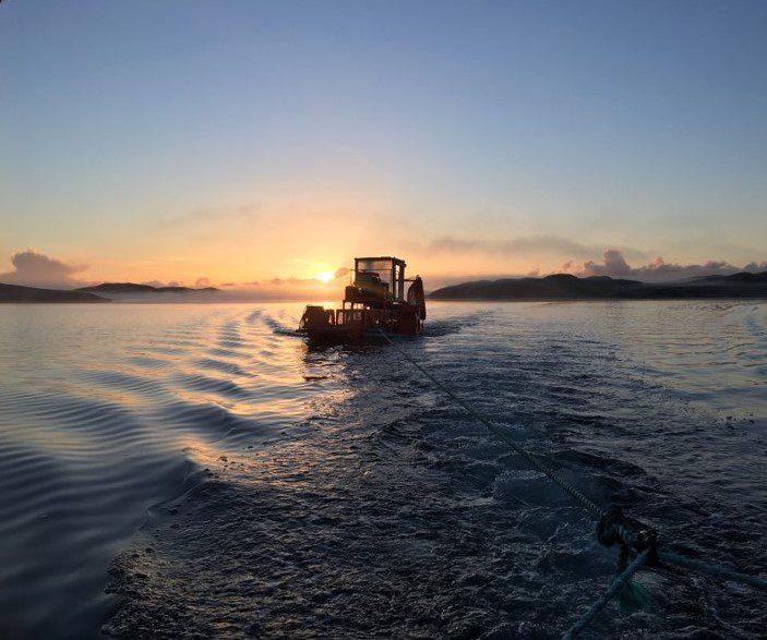 Harvesting seaweed in the Hebrides sea in Scotland